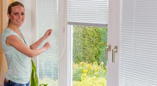 Eine Frau lässt bei einem Fenster die Jalousien herunter.